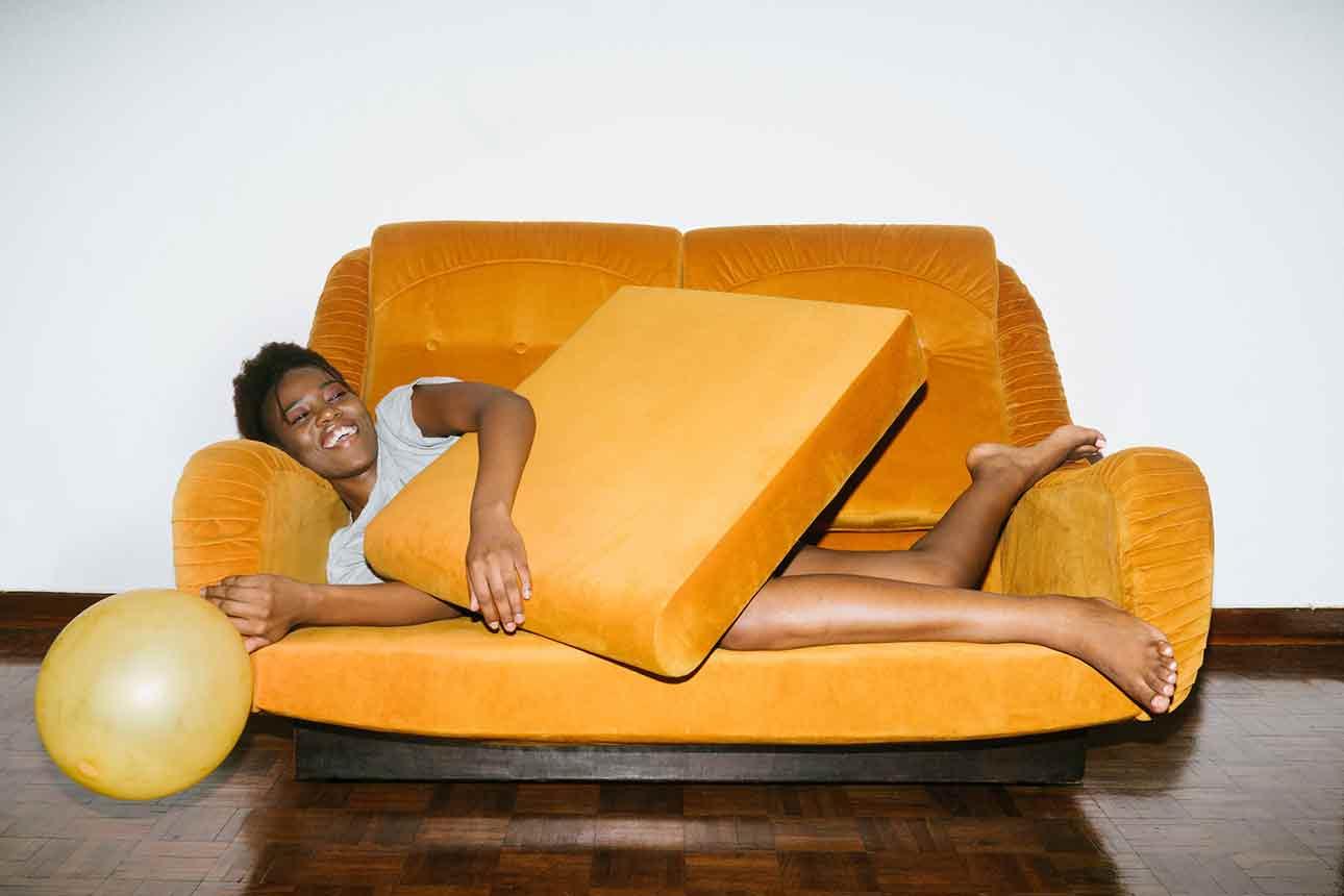 Jeune femme pétillante allongé sur un canapé de couleur vive