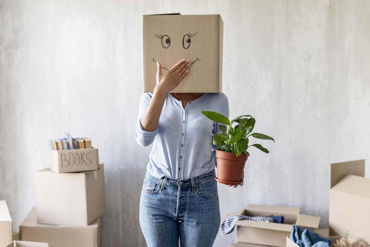 Une jeune femme à l'air malicieux qui cache sont visage sous un carton décoré d'un large sourire tout en tenant une plante dans sa main.